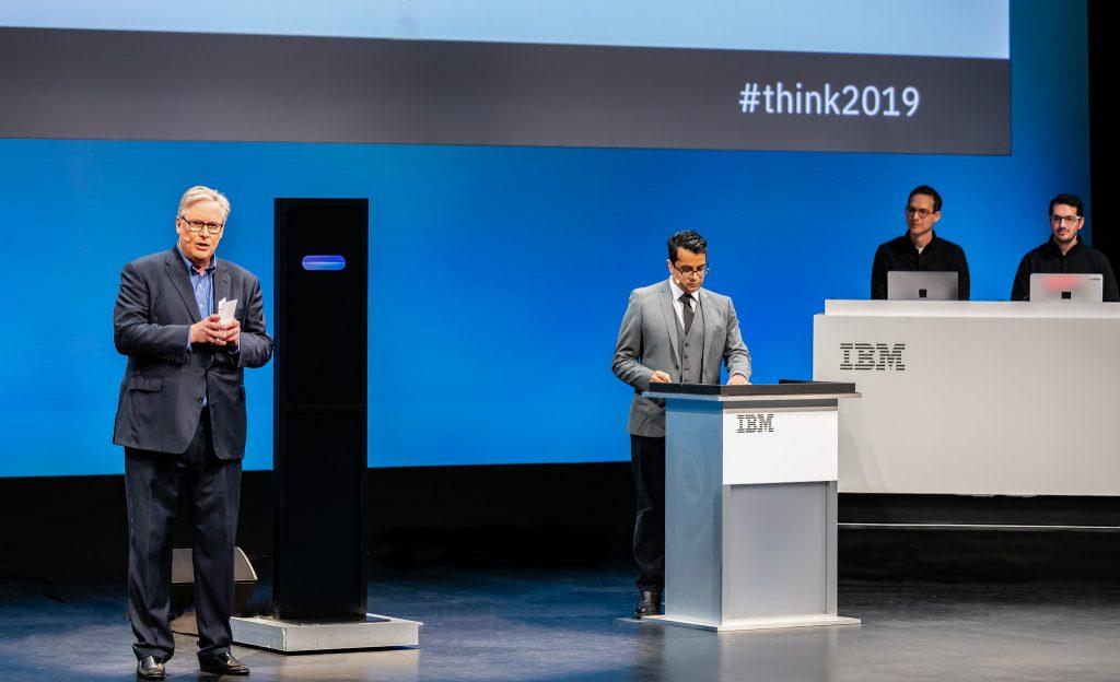 AIシステムであるIBM Project Debater(中央)とディベートの世界チャンピオンのハリシュ・ナタラジャン(右)が、「幼稚園/保育園に助成金を交付すべきである。」という論題について討論している様子