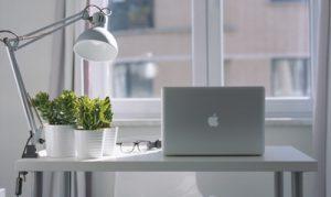 Bild av hemmakontor - dator, blomkrukor, lampa på bord framför fönster. Ledarskap på distans.