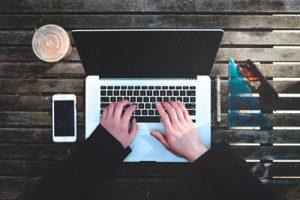 Laptop på utomhusbord, som någon skriver på - arbete och ledarskap på distans.