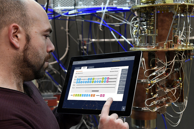 IBM Quantum Computing Research Scientist Antonio Corcoles uses the IBM Quantum Experience on a tablet in the IBM Quantum Lab that shows an open dilution refrigerator (Jon Simon/Feature Photo Service for IBM)