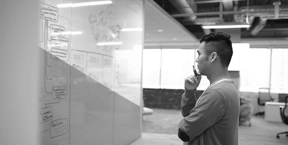 Creative businessman looking at white board