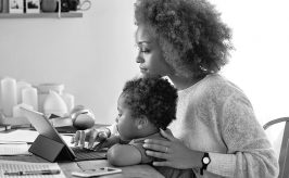 mother and child sitting at desk with tablet