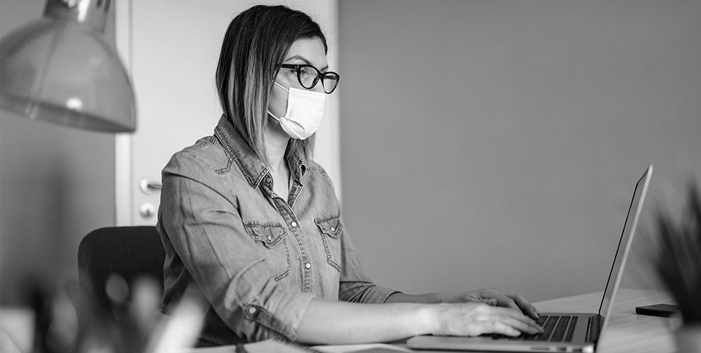 Woman with a mask on seated at desk and working on a laptop.