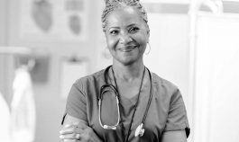 Woman wearing scrubs and stethoscope stands in clinical setting, smiling confidently
