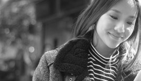 Black and white image of young lady checking smartphone