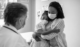 Mother holding young daughter, with masks on, in doctor's office