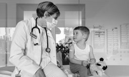 Pediatrician with face mask and toddler in medical practice