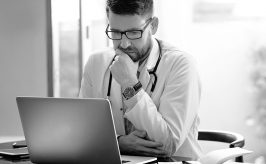 Male physician seated at desk looking at computer