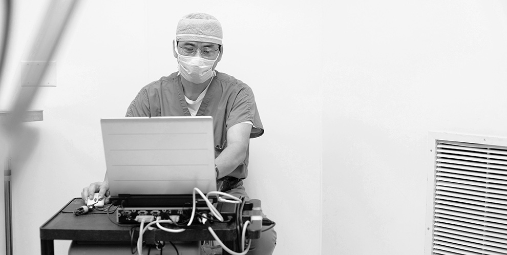 Doctor with scrubs on in hospital working on a computer