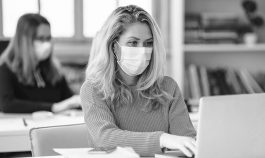 Two young women wearing masks work on laptops in an office environment