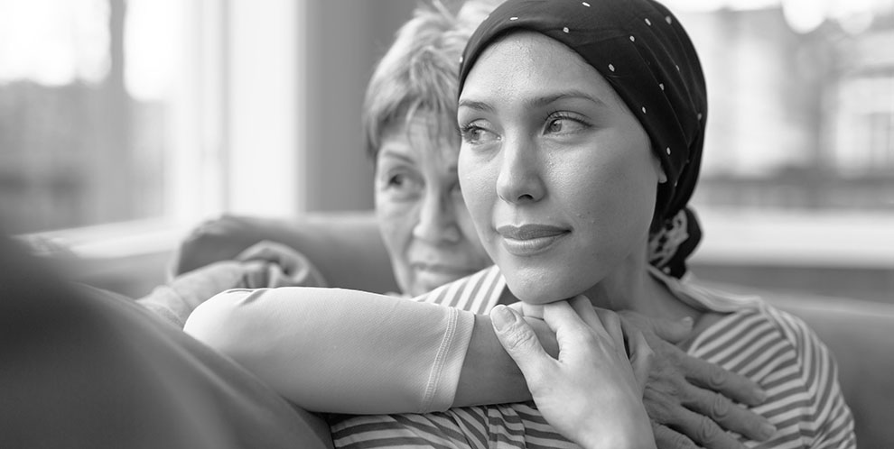 Oncology patient at home on couch receives hug from another woman