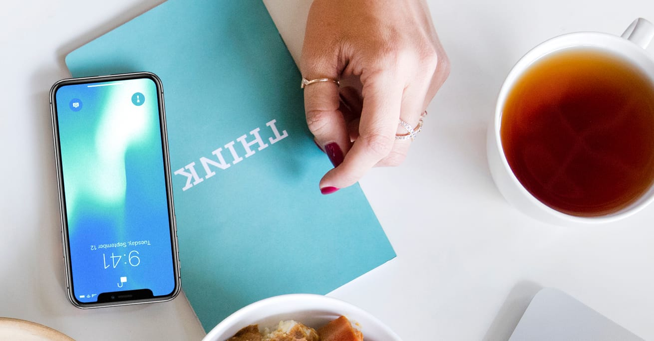 A smartphone, a light blue notebook with Think on the cover symbolic of why IBM, a cup of tea, a woman's hand and rice bowl.