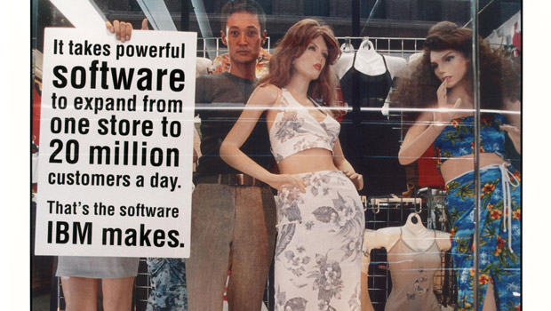 Man standing in a window with mannequins holding a sign that reads: It takes powerful software to expand from one store to 20 million customers a day. That's the software IBM makes.
