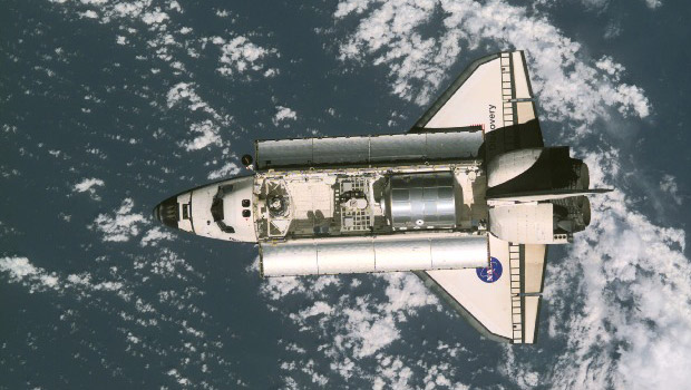The Space Shuttle Discovery with bay doors open and the word below it.