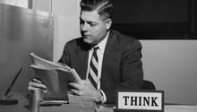 Man sitting at a desk with a Think plaque on it