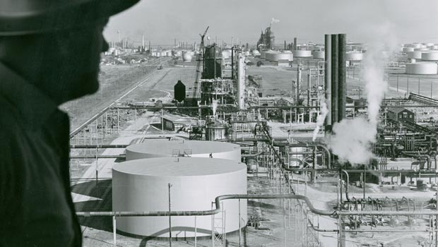 Man with an oil refinery in the background