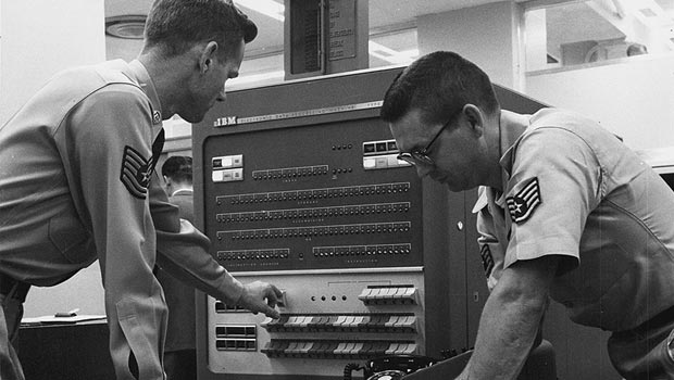 Two men working at the IBM 704