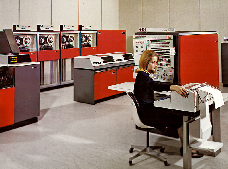 This is an image of a woman sitting at a printing apparatus with IBM 360 (specifically Model 40) in the background