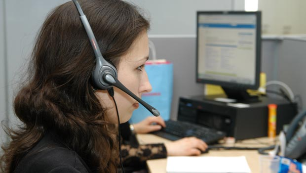 An employee takes a call at a call center