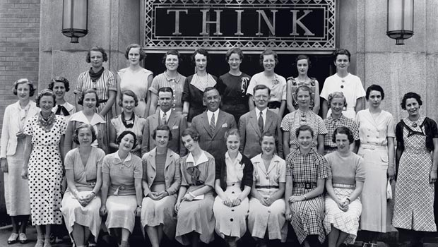 A class of system service women posed in front of a THINK sign