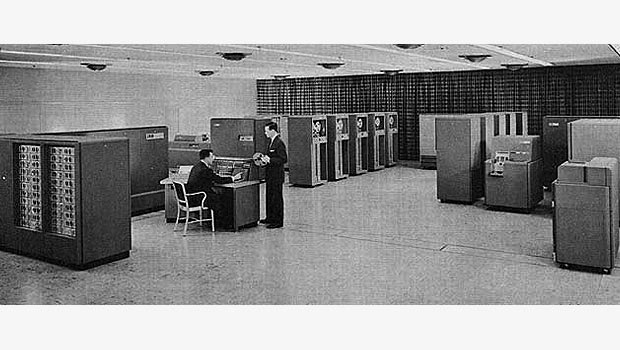 Large room full of IBM 700 Series components and two men working