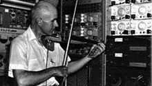 Man playing a violin standing next to IBM 700 series components