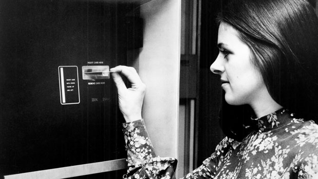 A woman uses a cash-dispensing ATM in 1972