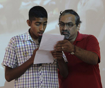 Arun Kumar (right) helping a student with his presentation during the certification ceremony at SSK—an emotional event for many who attend.