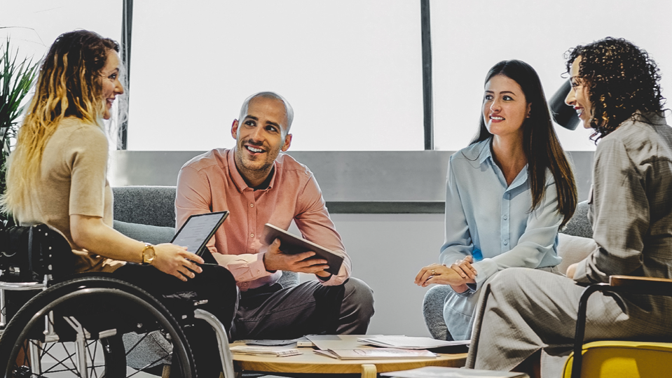 A woman in a wheelchair, a man and two women in a meeting.