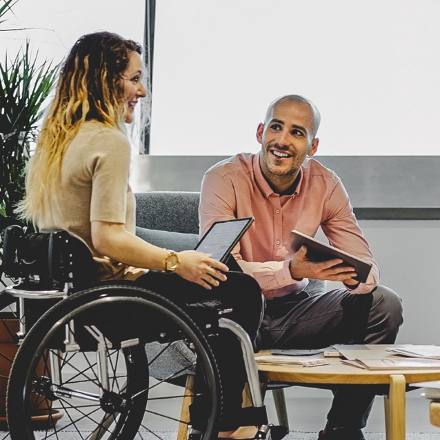 women in wheelchair talking to man that is sitting down in office