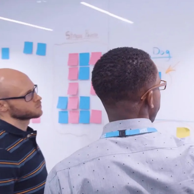 Two men standing in front of whiteboard with sticky notes on it