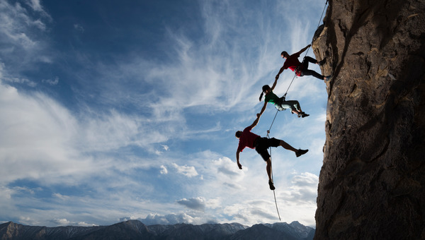 Three person repelling down cliff
