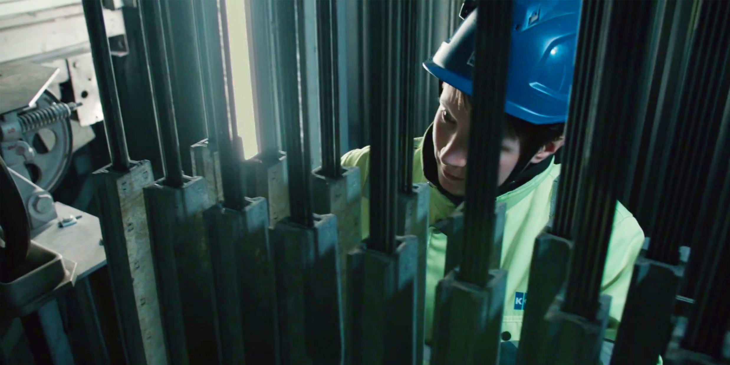 Worker wearing security equipment working with iron bars