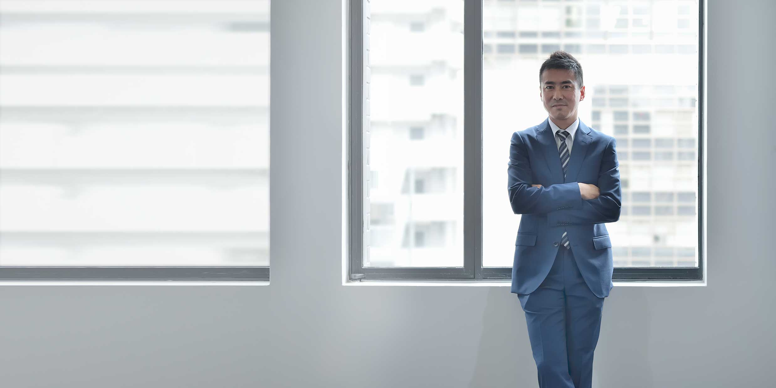 Man wearing executive clothes in front of a window