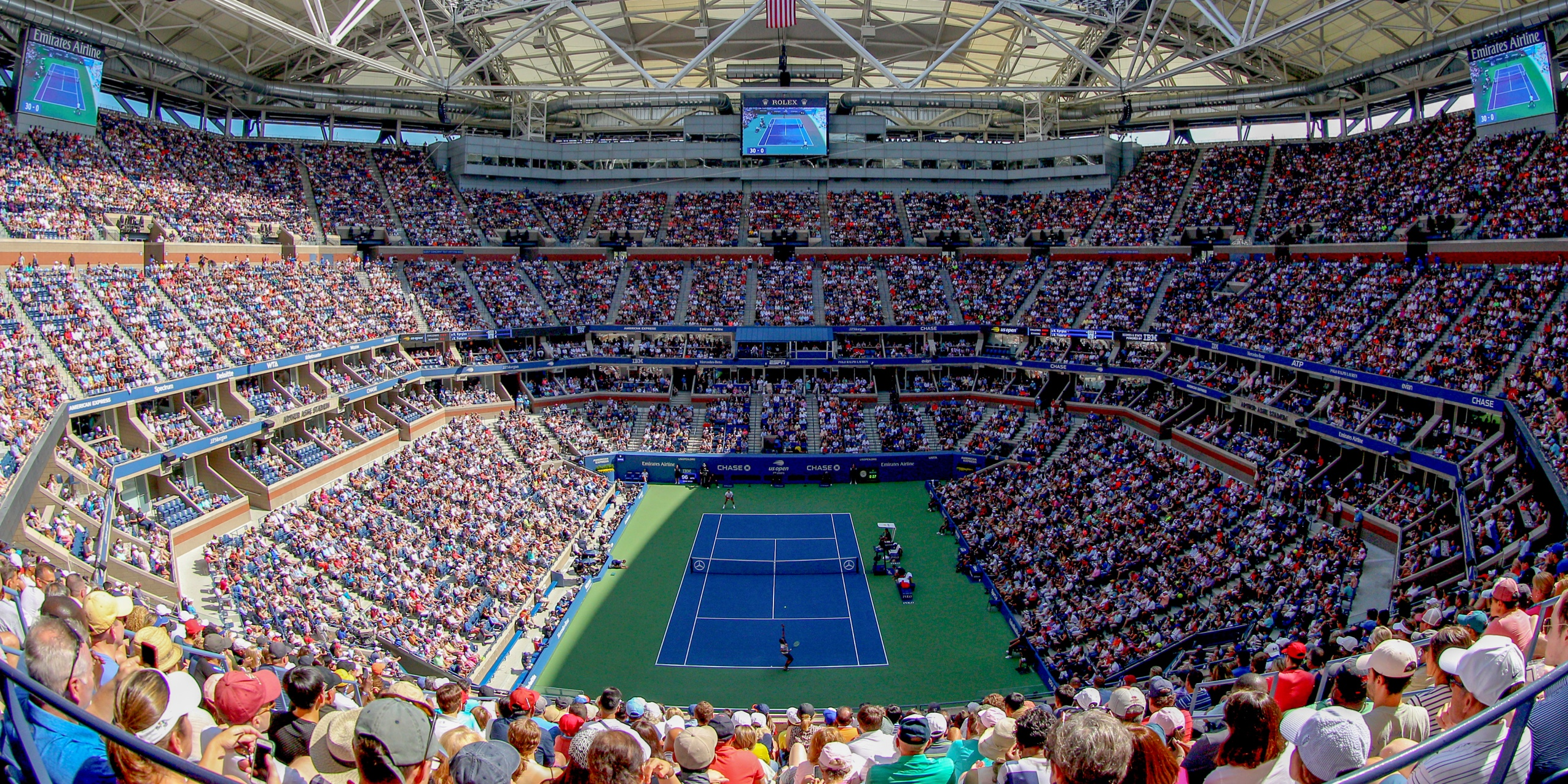 Panoramic photo of a crowded stadium watching a tenis match